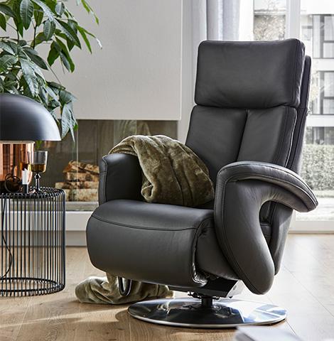 Schwarzer Relaxsessel aus Leder mit einer grünen Wohndecke