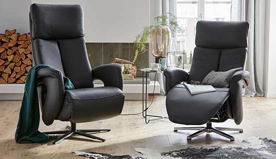 Zwei schwarze Sessel mit Relaxfunktion und einem gedeckten Beistelltisch