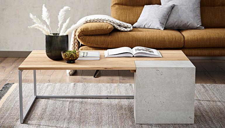 Moderner Couchtisch aus Holz mit einem Betonsockel vor einem braunen Sofa