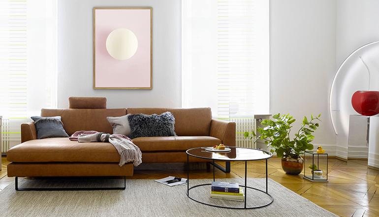 Cognacfarbenes Sofa neben rundem Beistelltisch und grüner Pflanze