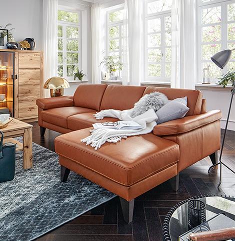 Hellbraunes Sofa mit Decke und grauem Fellkissen