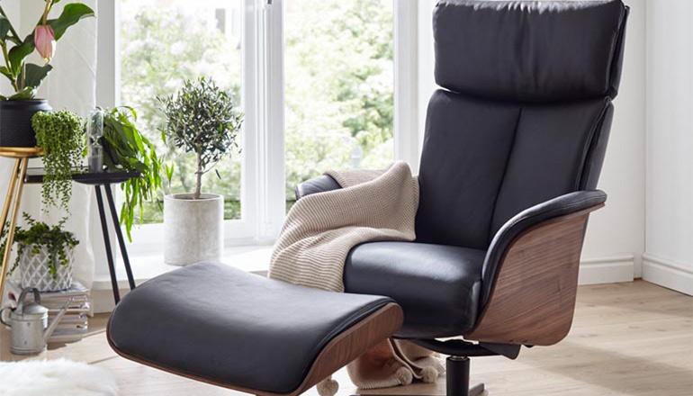 Schwarzer Lederrelaxsessel mit Armlehnschale aus Holz und dem dazu passenden Hocker