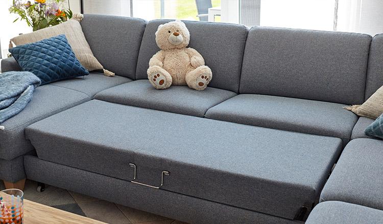 Blaue Wohnlandschaft mit Schlaffunktion und Deko-Kissen sowie einem Teddybären