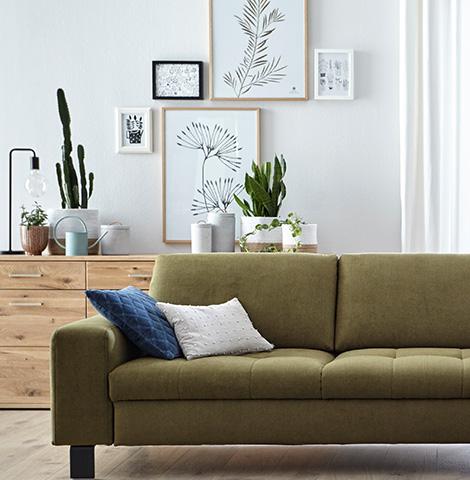 Gelbgrünes Sofa steht vor einem Sideboard aus hellem Holz