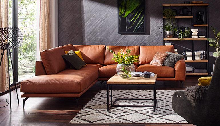 Cognacfarbenes Sofa neben Couchtisch aus Massivholz vor Bücherregal