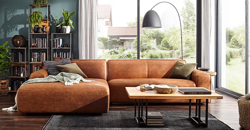 Gemütliches Sofa mit cognacfarbenem Lederbezug im hellen Loft
