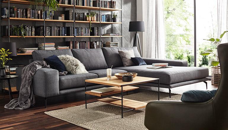 Couchtisch mit Massivholz und schwarzem Metall vor einem dunkelgrauen Sofa und Bücherwand