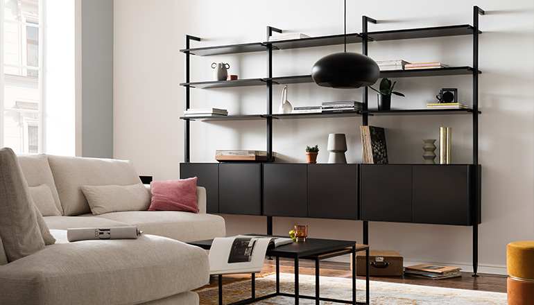 Schwarzes Regal mit Dekoration neben einem hellen Sofa und vor einer weißen Wand