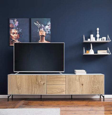 Lowboard mit heller Holzfront und weißen Regalen vor einer satten dunkelblauen Wandfarbe