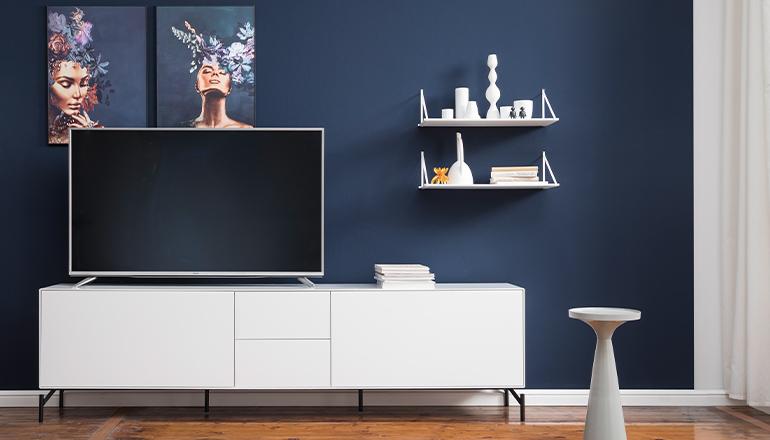 Zwei weiße Wandregale an einer blauen Wand über einem weißen Lowboard