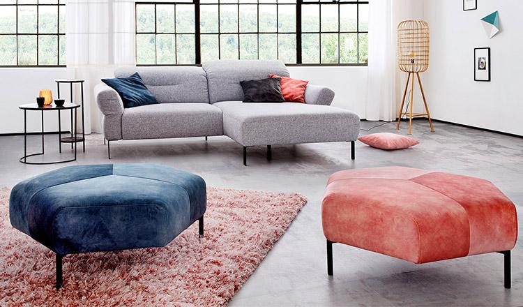 Zwei große farbige Hocker vor einem grauen 2-Sitzer Sofa mit Longchair