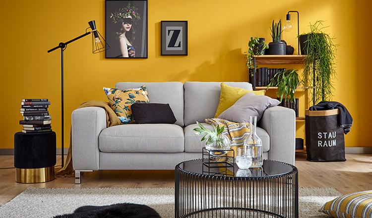 Hellgraues Sofa mit Deko-Kissen und modernem Beistelltisch vor einer gelben Wand