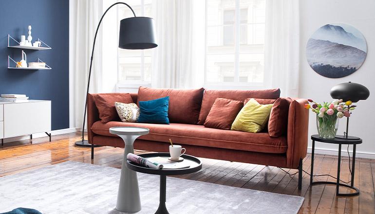 Kupferfarbenes 3-Sitzer Sofa mit bunten Deko-Kissen vor einer weißen Wand