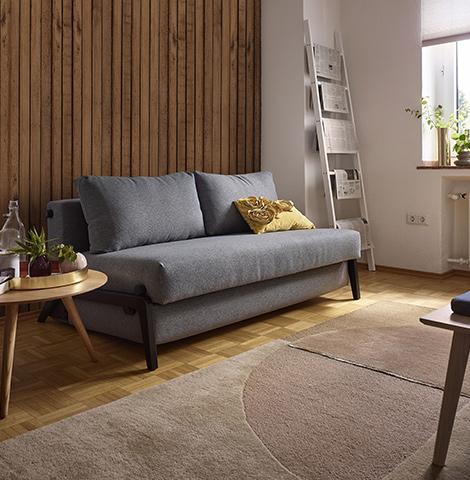 Graues Sofa mit Schlaffunktion und gelben Deko-Kissen neben einem runden Beistelltisch