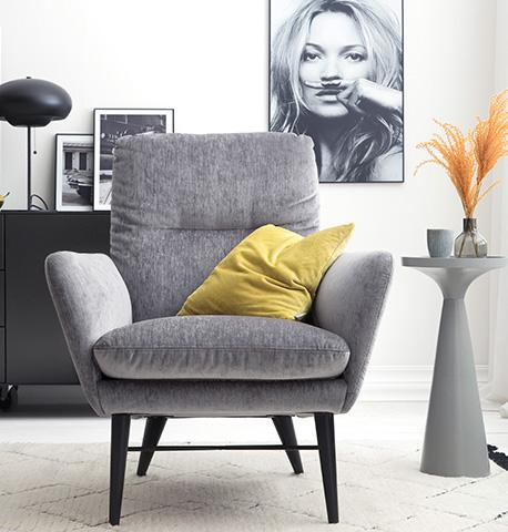 Grauer Sessel mit gelbem Deko-Kissen neben einem modernen Beistelltisch