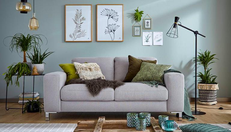 Hellgraues Sofa mit grünen Kissen, Pflanzen, Vasen und einer hellgrünen Wand