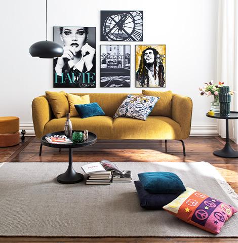 Senfgelbes Sofa aus dem Trendstoff Cord neben Hocker und Beistelltisch