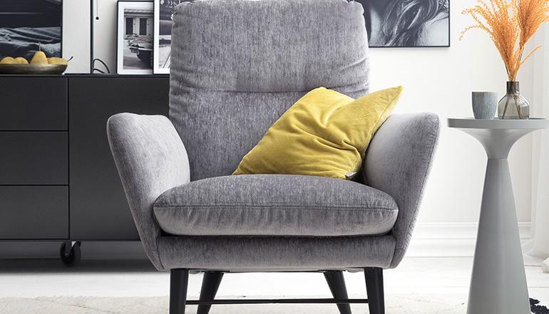 Sessel mit grauem Stoffbezug und gelben Deko-Kissen neben einem eleganten Beistelltisch