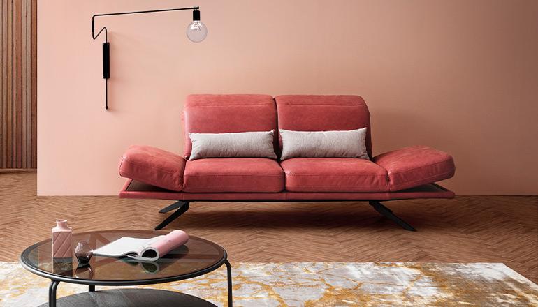 Rotes 2-Sitzer Sofa hinter einem dunklen, runden Beistelltisch