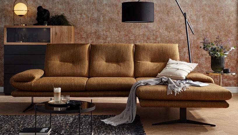 Braunes Sofa mit Longchair vor einer schwarzen Stehleuchte und einem Sideboard aus Massivholz