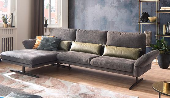 Graues Sofa mit Longchair und bunten Kissen in einem modernen Wohnzimmer