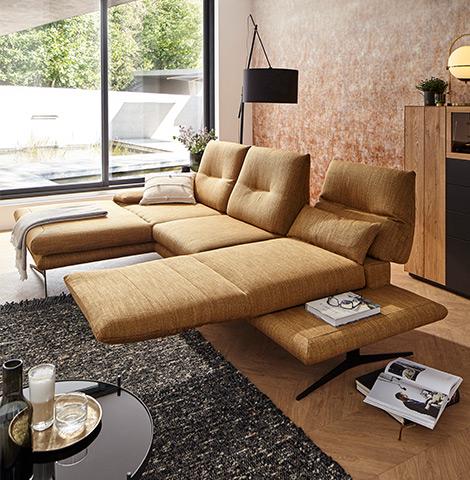 Braunes Ecksofa mit aufgebauter Relaxfunktion neben einer schwarzen Stehleuchte