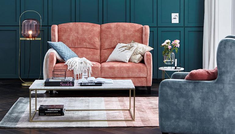 Pastellfarbenes Sofa im Pfirsich-Ton vor dunkelgrüner Wand