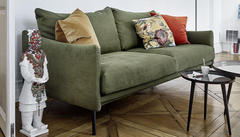 Grünes 2-Sitzer Sofa mit bunten Deko-Kissen und zwei runden Beistelltischen