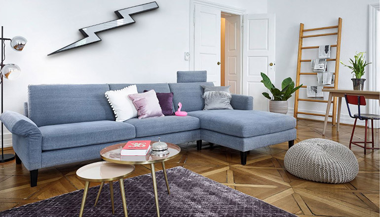 Hellblaues Sofa mit silbernem Pouf auf lila Teppich mit Retro-Couchtisch