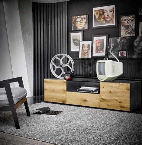 Wohnzimmer mit Lowboard mit Holzfront und Metall-Oberfläche und einer Bilder-Collage an der Wand
