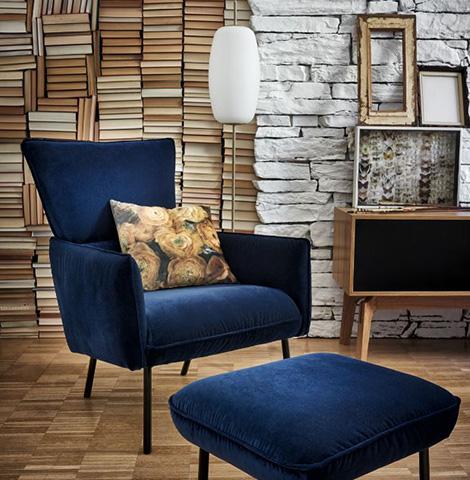 Blauer Loungesessel mit Deko-Kissen und passendem Hocker neben einem Lowboard