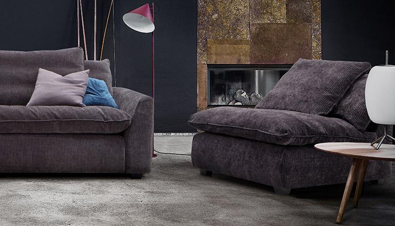 Sofa und Sessel mit dunkelgrauen Cordbezug vor einem Kaminofen