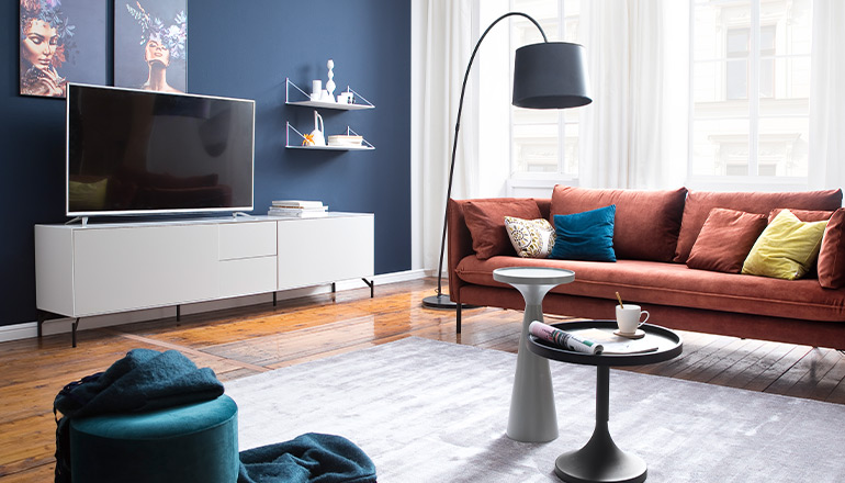 Weiße Wandregale an einer blauen Wand umgeben von einem Lowboard und einem Sofa