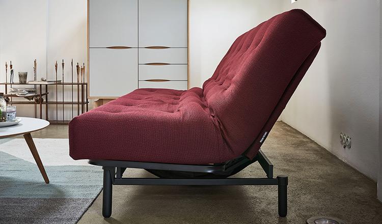 Seitenansicht eines roten Sofas mit Schlaffunktion vor einem Highboard