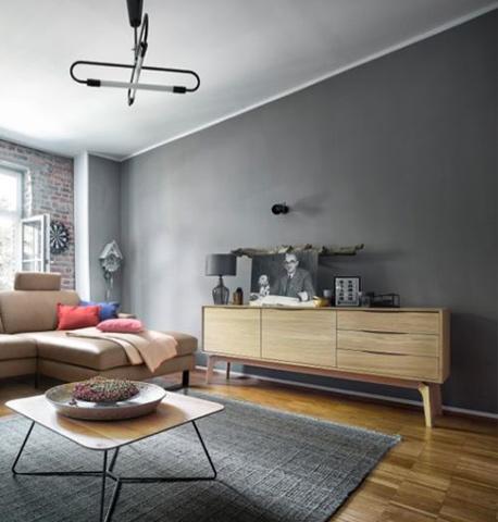 Lowboard aus Massivholz neben einem braunen Sofa sowie einem hölzernen Beistelltisch