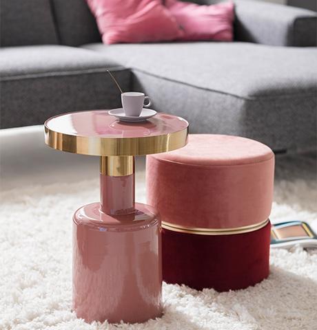 Rosa lackierter Beistelltisch neben einem roten und rosafarbenen Hocker