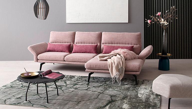 Rosafarbendes Zweisitzer Sofa vor grauem Teppich in Steinoptik