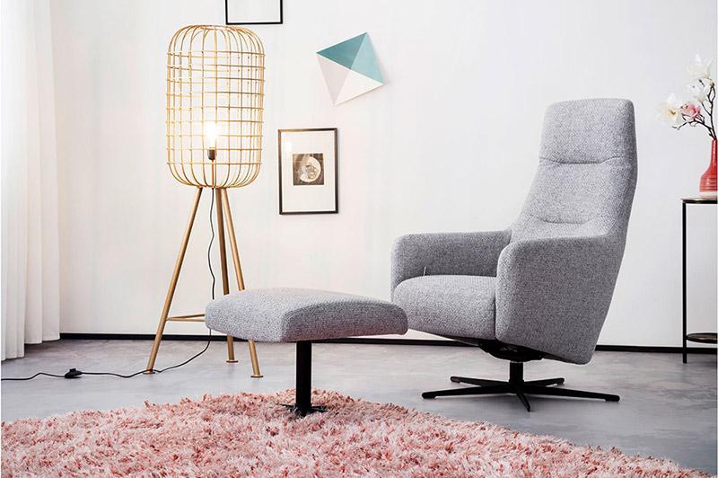 Hellgrauer Relaxsessel mit dem dazu passenden Hocker und eine Lampe im Skandi-Look
