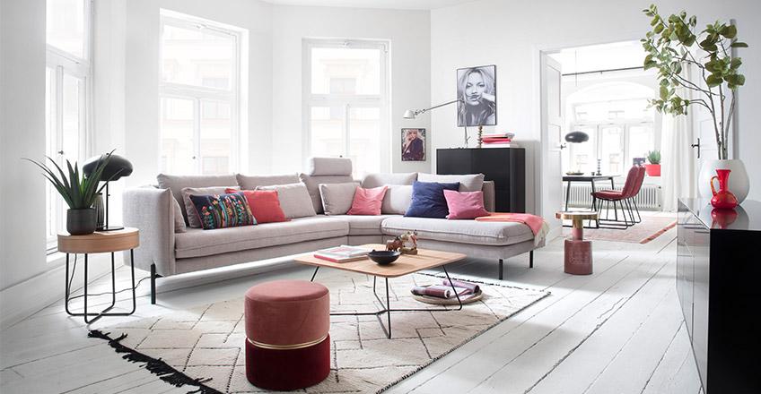 Hellgraue Couch mit bunten Kissen neben Beistelltischen und rosa Hocker