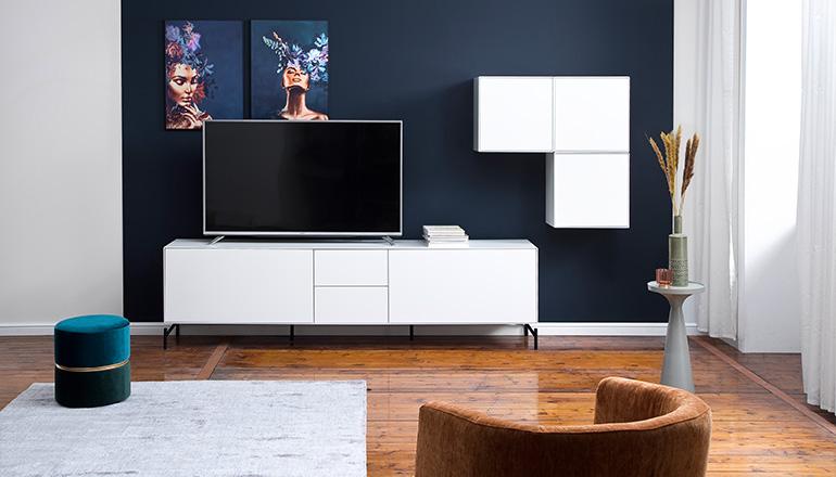 Weiße moderne Wohnwand mit Lowboard und Hängevitrine im Skandi-Stil vor einer dunkelblauen Wand