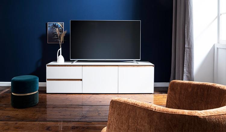 Weißes Lowboard mit einem Fernseher vor einer blauen Wand