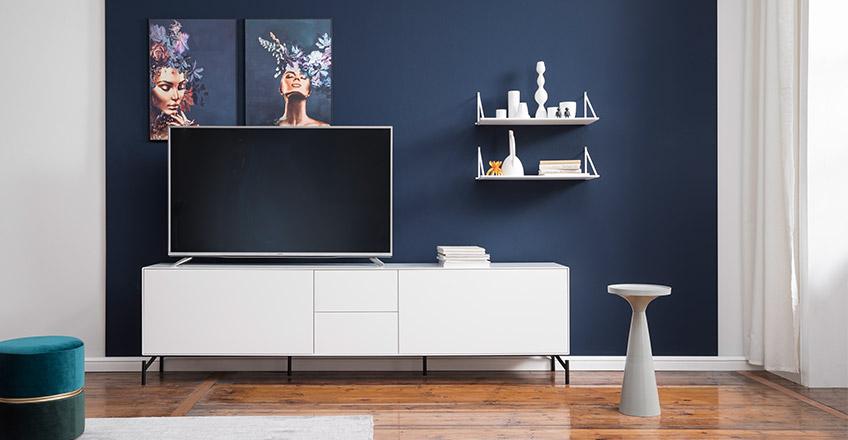 Weißes Lowboard vor einer dunkelblau gestrichenen Wand im Wohnzimmer