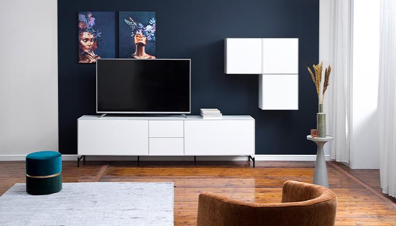 Weiße Wohnwand vor dunkelblauer Wand und einem cognacfarbenen Sessel